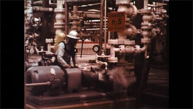 UNITED STATES 1970s: Hydrogen Sulfide (H2S) Gas Leaking From Faulty Pump Whilst Worker carries Out Inspection