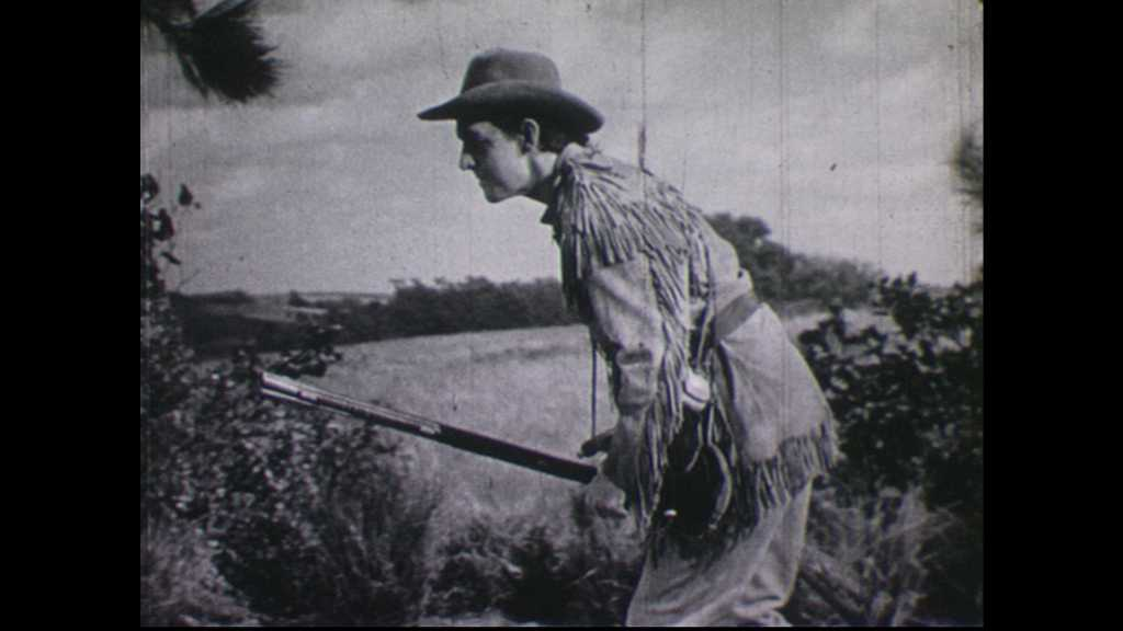 1940s: Man crouches and fires rifle.  Native Americans on horseback shoot guns at house.  Shots come from windows.