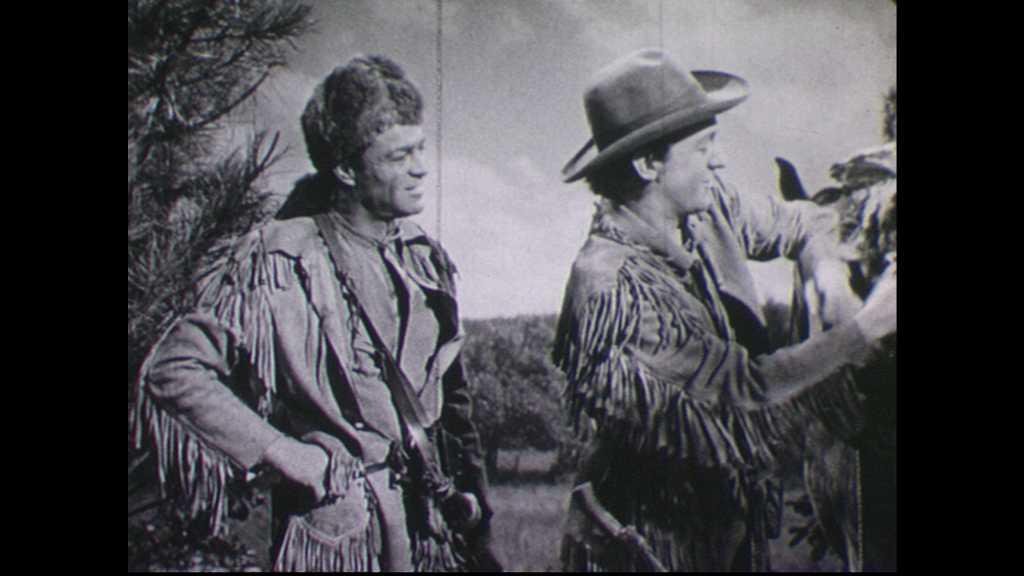 1940s: Man secures pelts on horse.  Men speak.  Men hear a sound.
