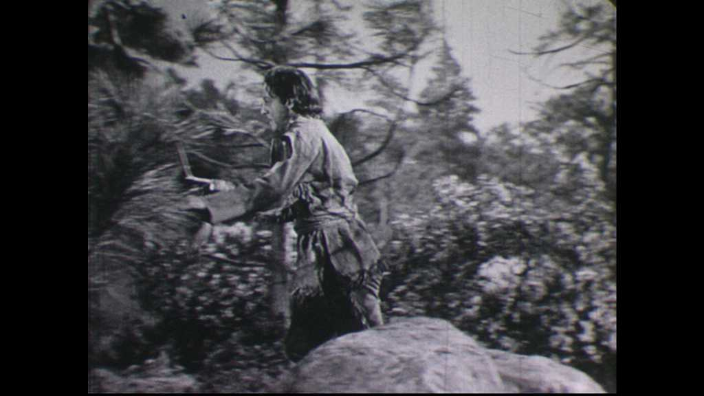 1940s: Man runs through woods. Man chops wood. People run up stairs, into fort. Native Americans ride on horseback. Man shoots rifle from behind fort wall.