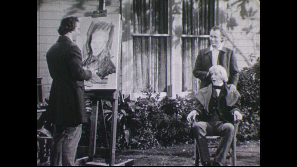 1940s: Old man sits in chair, talks. Young man stands behind old man. Man paints portrait of old man.