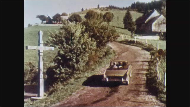 1960s: People in small convertible car drive up windy, dirt road, passed cross on side of road and up hill. Car stops and three people get out to look at sights.