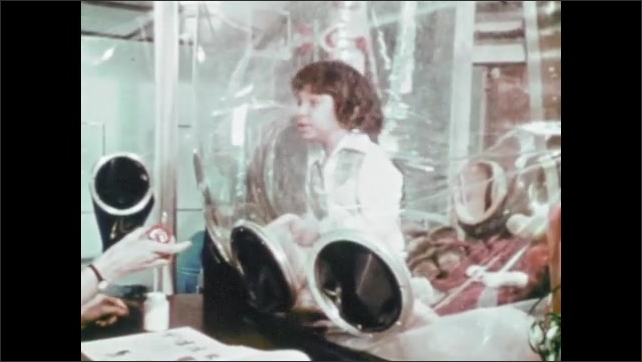 1970s: Boy in isolation chamber in hospital places hands into gloves. Woman hands jar of paste to boy.