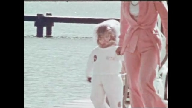 1970s: Girl wears mobile isolation suit. Woman and girl walk down dock. Woman bounces girl on playground equipment. Girl rides playground pony.