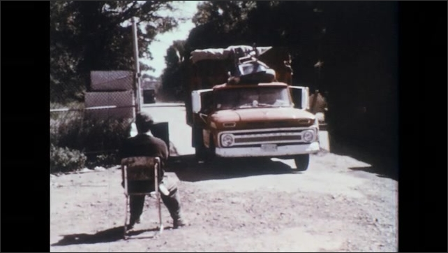UNITED STATES 1970s: Garbage trucks enter a site as a checker keeps track of their entry.
