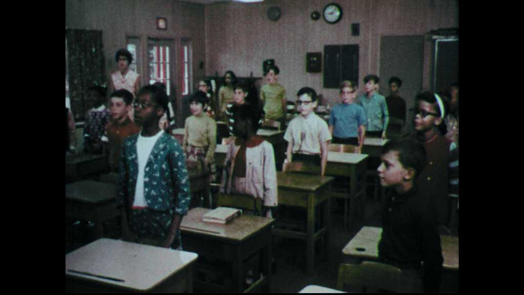 1960s: Students stand at desks in classroom sing