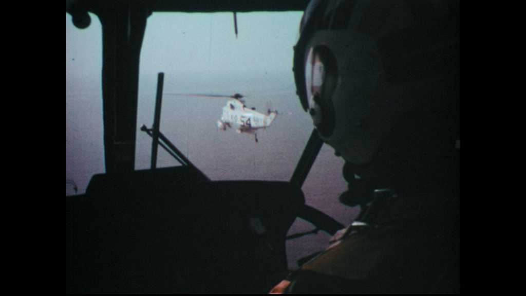 1960s: Navy helicopters fly above the ocean,. Pilots scan the waters.