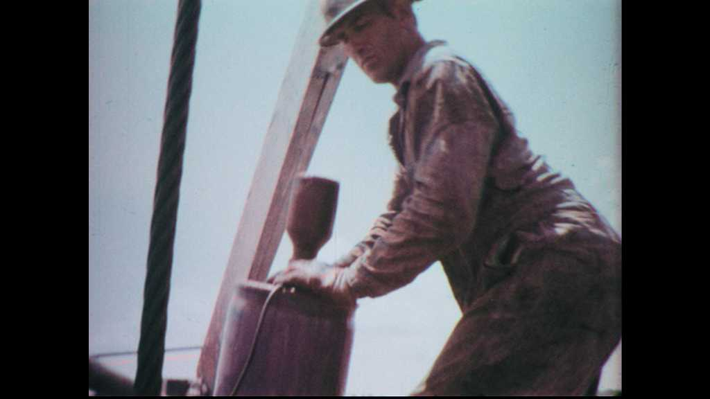 1960s: Man works on oil rig. Machinery rotates on oil pump.