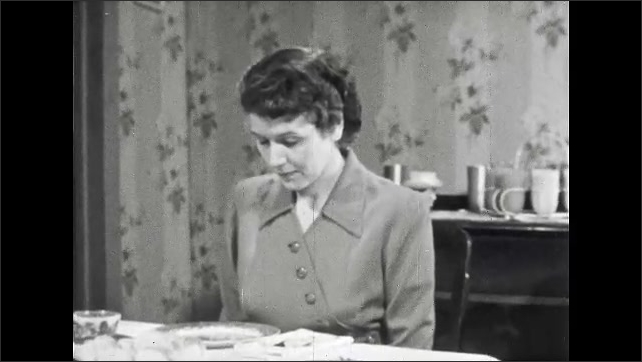 1950s: UNITED STATES: Lady bows head at table.