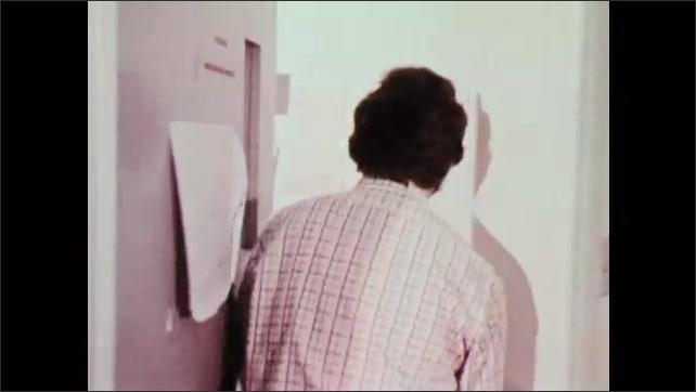 1970s: UNITED STATES: tornado destroys building. News room alarm sounds in tornado situation. Man speaks on radio.