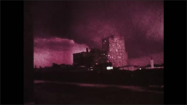 1970s: UNITED STATES: funnel touches down by city and heads downtown. Head cameraman films tornado from roof of building.