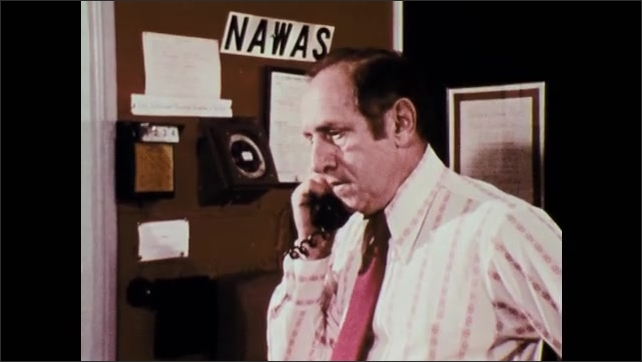 1970s: UNITED STATES: man in uniform at civil defence. Director of civil defence makes call.