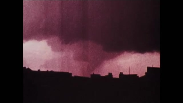 1970s: UNITED STATES: police car on road. Funnel rips past Ohio River near Cincinnati. Debris in air by clouds.