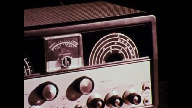 1970s: UNITED STATES: close up of radio. Workers in civil defence centre.