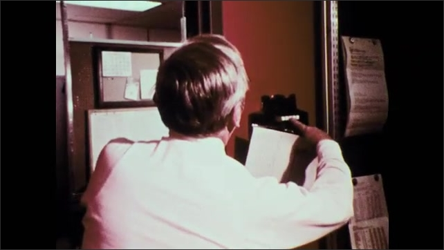 1970s: UNITED STATES: lady in kitchen talks on telephone. Man speaks on phone in office. National weather service office workers.