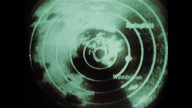 1970s: UNITED STATES: radar view and echo of tornado. Men at police station follow tornado.