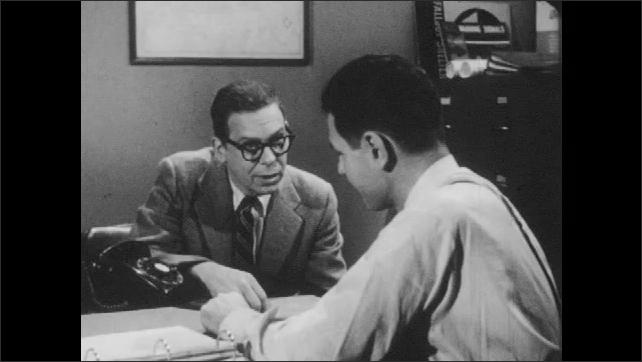1960s: Civil defense director and man talk at desk.