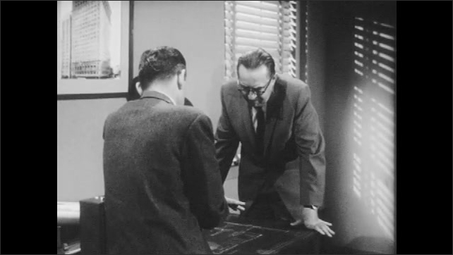 1960s: Civil defense director and another man review and discuss blueprints.