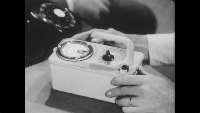 1960s: Civil defense director studies equipment as another man talks.
