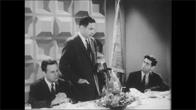 1960s: Civil defense director gives speech while others listen in deep thought.