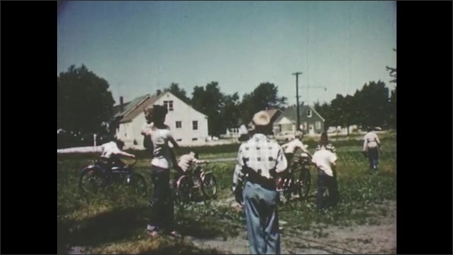 1950s: A group of kids leaves an empty lot. Kids climb on bikes and walk away.