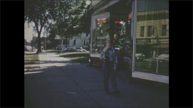 1950s: Young boy holds puppet and walks slowly away from store, kicks at littler on the ground.