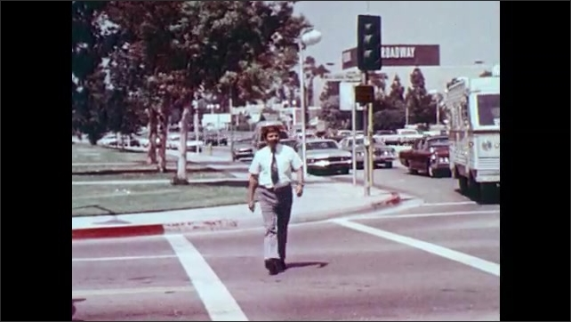 1970s: cars drive by green light. man in tie looks both ways and behind and crosses as street with men and women near recreational vehicle. man walks on sidewalk, stops at crossing and observes.