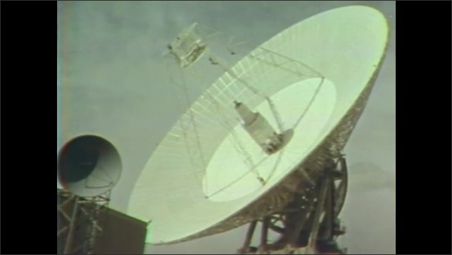 1960s: Large deep space satellite dishes. Men at consoles talk on telephones.