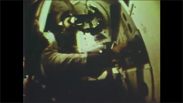 1960s: Astronaut moves through spacecraft, looks through eyepiece, flips into seat.
