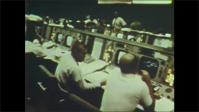 1960s: Lit buttons on a console. People work at consoles in mission control. Man adjusts diagram on board.