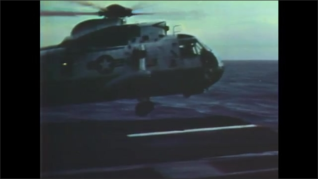 1960s: Men in control room watch helicopter land. Helicopter lands on aircraft carrier.