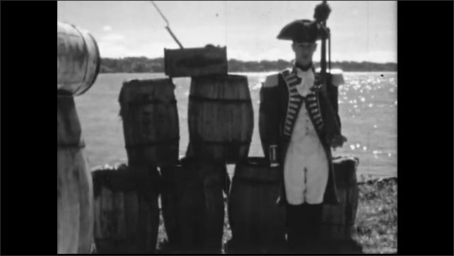 1940s: Man reads from scroll. Patriot stands by barrels at water's edge as armed soldier marches behind him. Cannon fires. Window opens and musket is aimed outside.