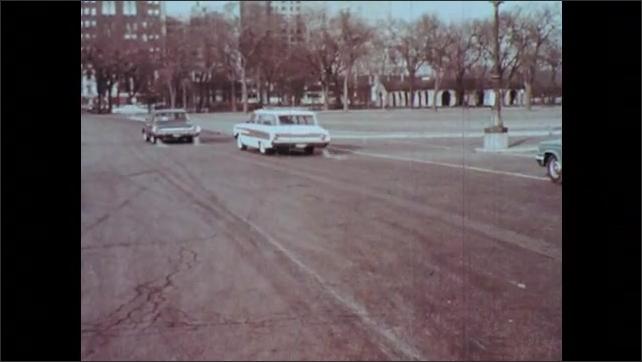 1960s: Man waves glove.  Policemen.  Cars drive away.
