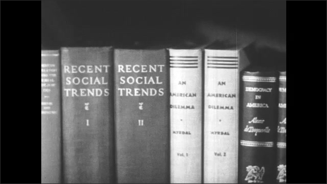 1950s: Man stands up from desk, walks to book shelf. Man opens books shelf, talks into camera. Pan across books.