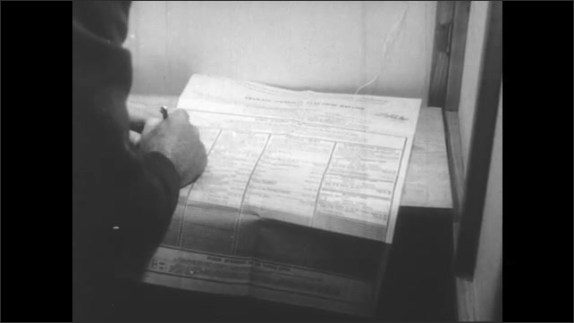 1950s: Men enter voting booths. Hand writes on ballot. Officers at desk, man approaches desk.