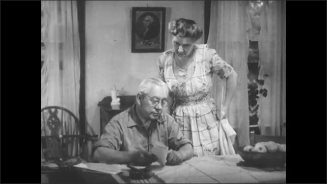 1950s: Animation of houses on plots of land. Man at table, woman approaches. Close up of paper in hand. Man and woman at table.