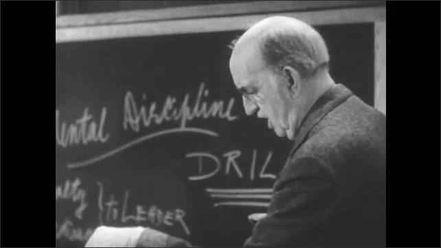 """1950s: Classroom of a teacher's college, chalkboard reads """"Mental Discipline"""" and """"DRILL."""" Teacher seated at desk, man lectures passionately from podium."""
