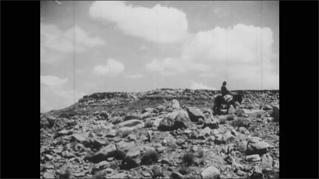 1940s: UNITED STATES: man rides donkey across arid landscape.
