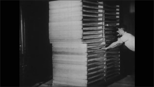 1940s: UNITED STATES: man pushes cartons of dried carrots in factory. Secondary tunnel in dehydration factory. Men pull down screen