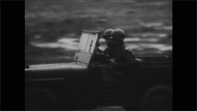 1940s: UNITED STATES: jeep drives through war zone with food supplies for soldiers. Soldiers load dehydrated food into truck