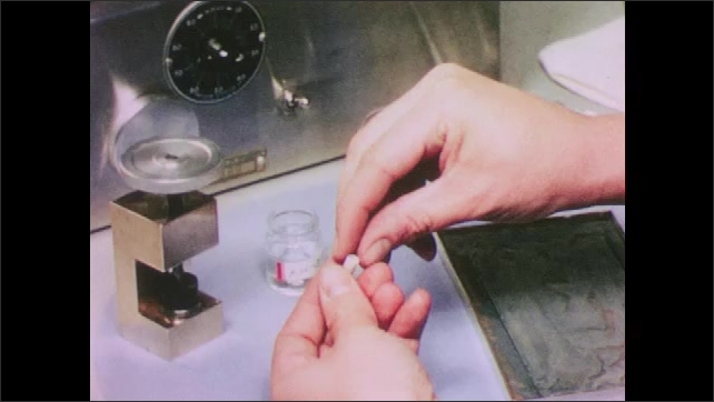 1950s: UNITED STATES: hand screws lid on container. Hand draws on specimen with pencil. Hand places specimen into machine