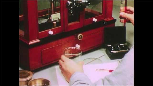 1950s: UNITED STATES: powdered specimen in controlled environment. Man writes notes from observations. Man turns dial. Man pours water into container. Man puts glass lid on container