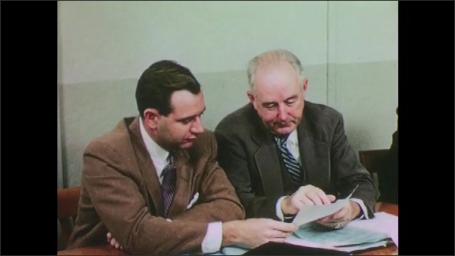 1950s: UNITED STATES: men talk in board room meeting at research facility. Men share notes in meeting. Men discuss specifications and certifications for materials