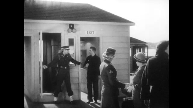 1950s: UNITED STATES: operator inspects bags of visitors. Man leaves building through exit. Metal object detected on screen.