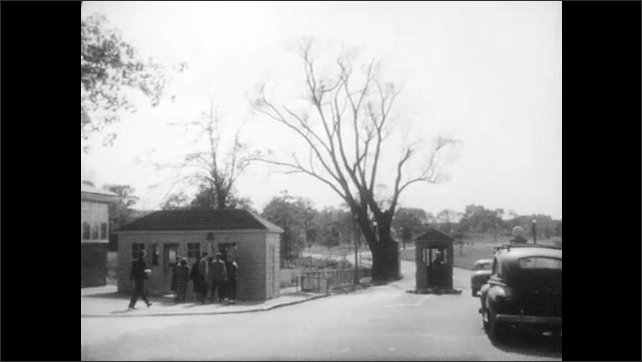 1950s: UNITED STATES: vehicle at military check point. Vehicles pass through check point. Fence around military base.