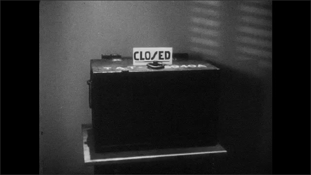 1950s: UNITED STATES: man observes base from look out point. Lock on gate. Locked steel cribs. Closed sign on counter. Man works at desk.