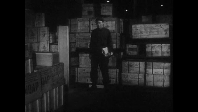 1950s: UNITED STATES: guard patrols warehouse. Man walks around boxes. Casual pilferer in warehouse. Man steals from box.