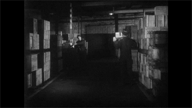 1950s: UNITED STATES: guard catches pilferer in warehouse. Guard covers prisoner. Guards arrive at warehouse