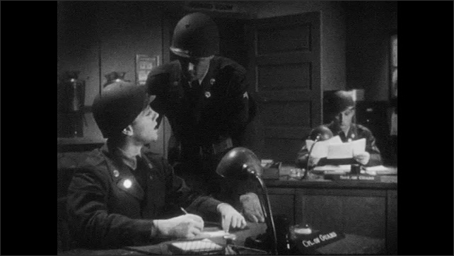 1950s: UNITED STATES: guard stands by box. Guards work in office. Men write report at desk. Security Officer reads report