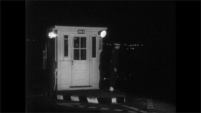 1950s: UNITED STATES: military police man waits at gate. Guard patrols post.